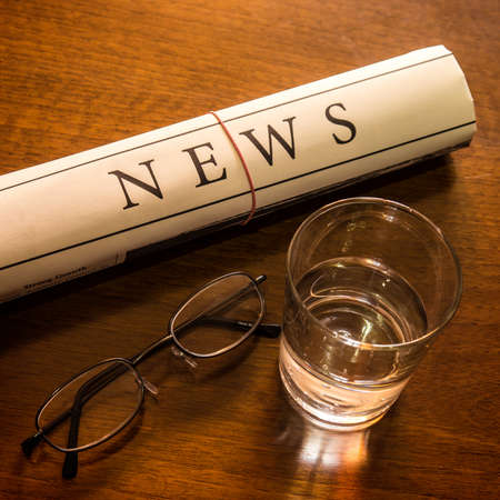 lates: newspaper, glass water, glasses on desk Stock Photo