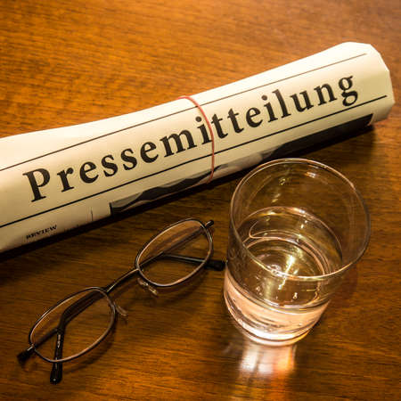 lates: pressemitteilung newspaper, glass of water, glasses on desk