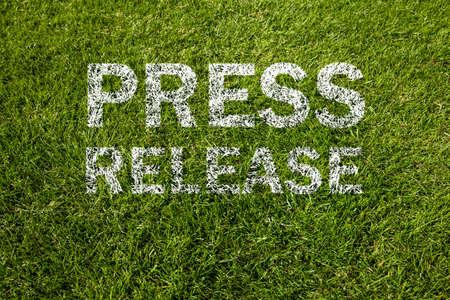 press release in white letters on meadow
