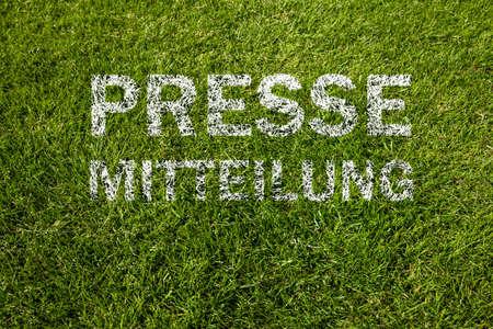 press release (pressemitteilung german) in white letters on meadow Reklamní fotografie
