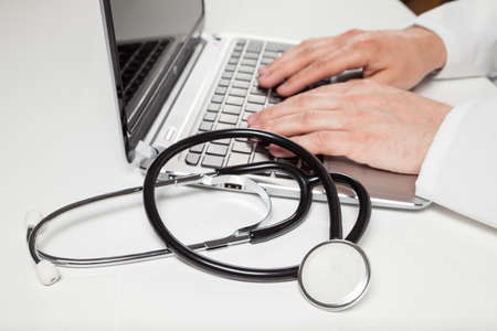 pratice: doctor typing on laptop on desk