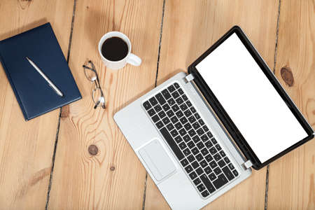 laptop, cup of coffe and notebook on wooden floor