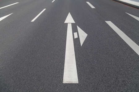 ambivalent: arrow in two directions on asphalt
