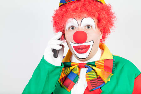 ballyhoo: marvelling clown with smartphone on white