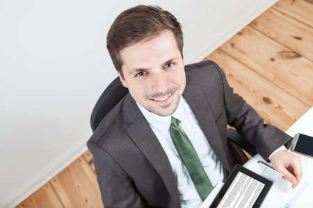 smiling businessman in office with wooden floor photo