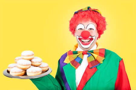 ballyhoo: clown with berlin pancakes on yellow background