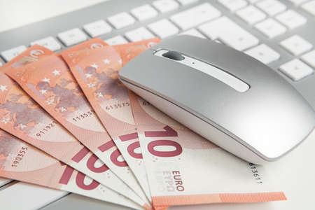 50 euro: 50 euro banknotes on keyboard and mouse Stock Photo