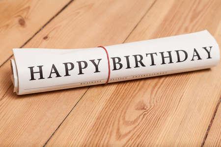 happy birthday newspaper on wooden floor Foto de archivo