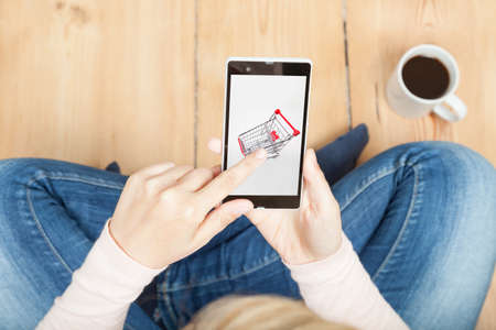 woman typing on shopping cart on smartphone