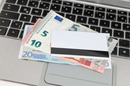 misuse: bank card and euro cash on laptop Stock Photo
