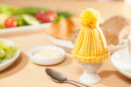 cosy: egg with egg cosy on breakfast table Stock Photo