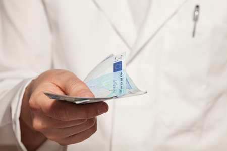 doctor holding gift: Doctor with banknotes Stock Photo