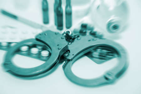 Handcuffs and medicine Stock Photo