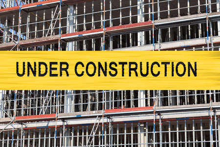 building sector: under construction writing, background scaffold Stock Photo