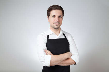 shop assistant: shop assistant with apron on grey background (supermarket; coffee bar)