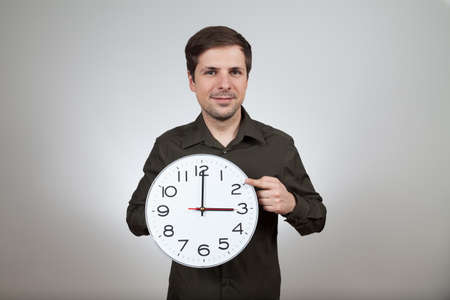 wintertime: man shows clock change to wintertime
