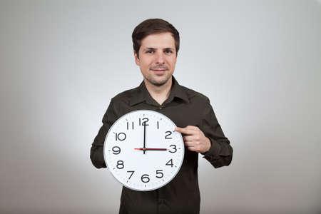 wintertime: man shows clock change to wintertime