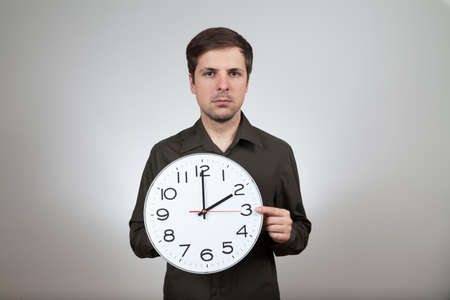 man shows clock change to summertime
