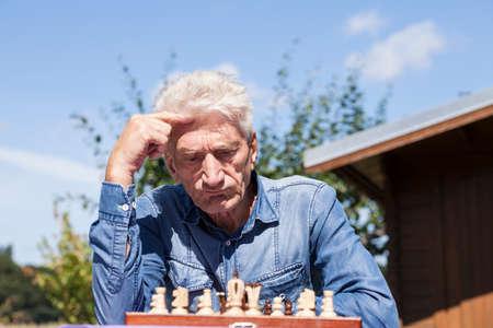 tablero de ajedrez: Pensionista con tablero de ajedrez Foto de archivo