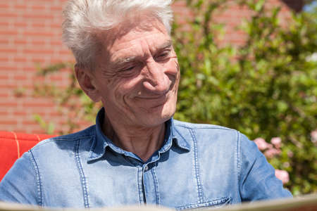 pensioner: Pensioner reads amused the newspaper