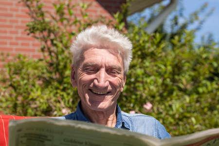 amused: Pensioner reads amused the newspaper