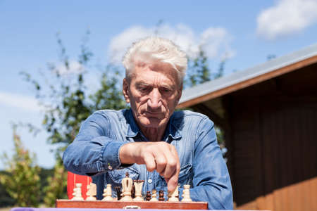 playing chess: Man playing chess in garden Stock Photo
