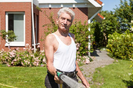 motivated: Man pours motivated his garden Stock Photo