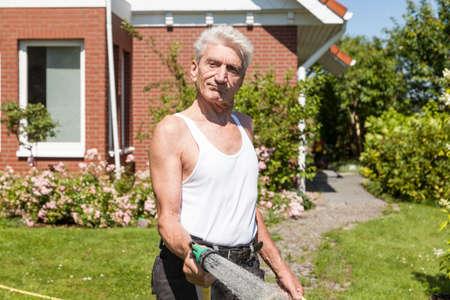 water garden: Man pours motivated his garden Stock Photo