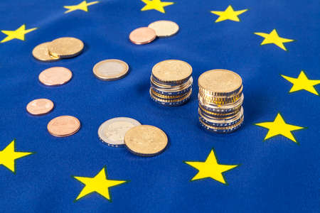 EU flag and Euro coins Stock Photo