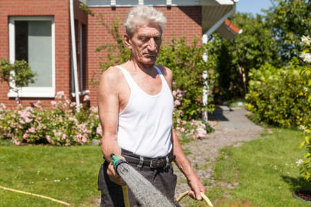 sullenly: Retired sullenly pouring the garden Stock Photo