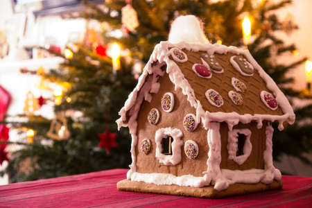 gingerbread house: Gingerbread house with christmas tree in background Stock Photo