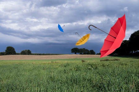 blustery: Umbrellas and storm clouds Stock Photo