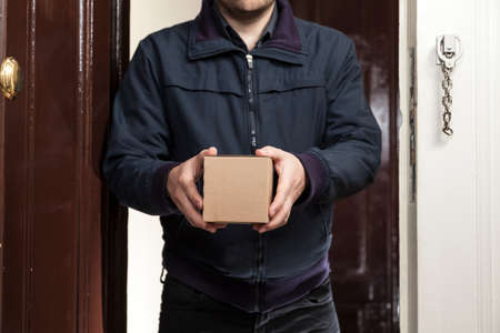 delivers: Postman delivers a small package Stock Photo