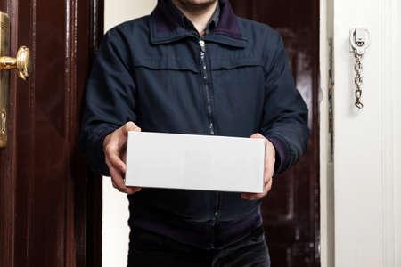 brings: Postman brings a white package