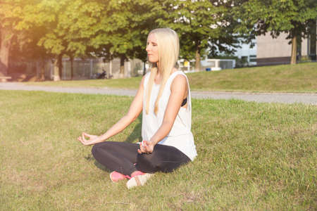 sittting: Young woman doing yoga in sunlight
