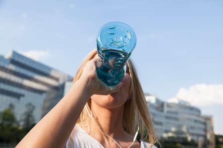 or thirsty: Mujer sediento que bebe agua de una botte Foto de archivo