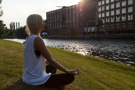 sittting: Woman doing yoga (lotus position) in Berlin at Spree