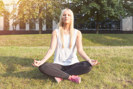 sittting: Young woman doing yoga (lotus position)