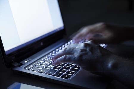 grabber: hacker on laptop in dark room Stock Photo