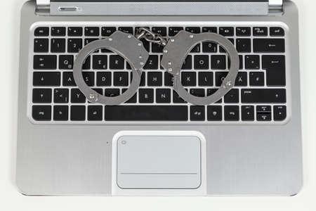 handcuff: handcuff on keyboard of laptop