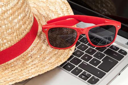 chapeau de paille: chapeau de paille, lunettes de soleil et un ordinateur portable Banque d'images