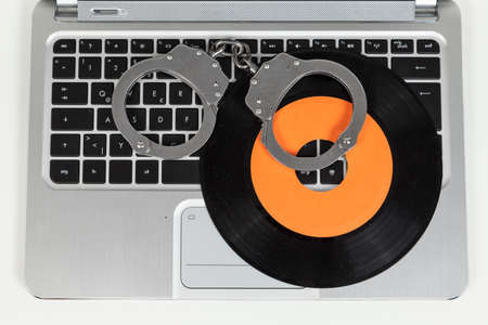 manacle: handcuff and record on a laptop Stock Photo