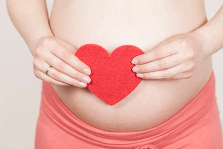 cordially: Expection mother holding red heart Stock Photo