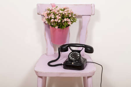 outmoded: Old-fashioned phone and flowers on chair