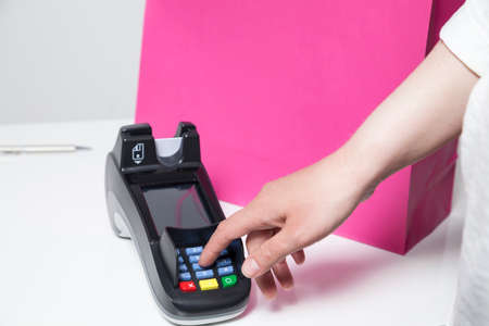 pin code: Woman entering Pin Code in a reading device for payment in a shop