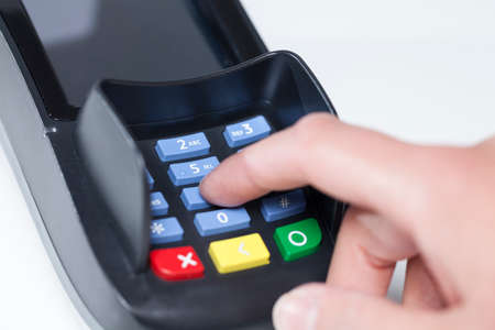 pin code: Entering Pin Code in a reading device for payment in a shop Stock Photo