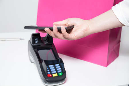epayment: Woman paying with smartphone (mobile payment) in a shop