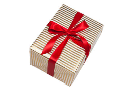 Christmas present with golden stripes and red ribbon on white Standard-Bild
