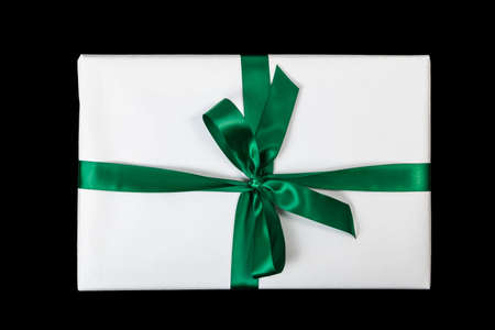 White christmas present with green ribbon on black background (top view) Standard-Bild