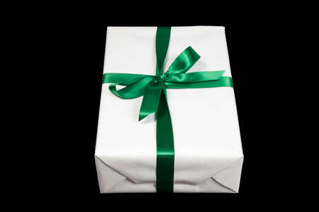 White christmas present with green ribbon on black background